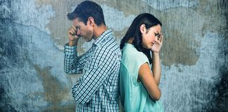 Composite image of depressed couple standing back to back. Depressed couple standing back to back against rusty weathered wall Stock Images