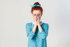 Depressed and crying young caucasian girl with ginger hair feeling ashamed or sick, covering face with both hands. Portrait of unhappy, depressed and crying stock photos