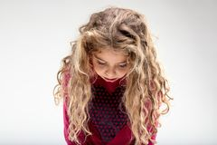 Sad curly-haired schoolgirl with head down. Depressed curly-haired preteen girl with head down Stock Photo