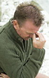 Depressed and dejected man. An upset and depressed forties man shows the strain as he holds his head Royalty Free Stock Photos