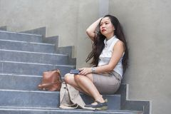 Depressed and desperate Asian Chinese businesswoman crying alone sitting on street staircase suffering stress and depression. Young depressed and desperate Asian stock photos