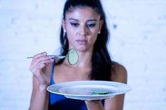 Depressed dieting woman holding folk looking at small green vegetable on empty plate stock photography