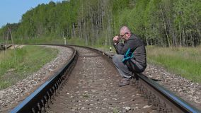Depressed disabled man with crutches sitting on railway and crying stock video footage