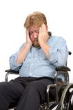 Depressed Disabled Man In Wheelchair. Worried and depressed disabled man in a wheelchair holds his head in his hands Stock Photos