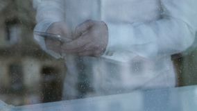 Depressed divorced man texting from smartphone, rain dropping on window glass. Stock footage stock video footage