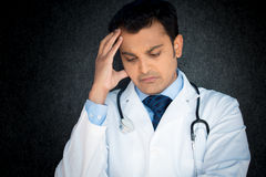 Depressed doctor. Closeup portrait, young depressed man healthcare practitioner holding face in despair,  black gray background Stock Photography