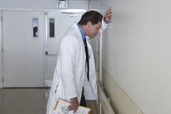Depressed Doctor Leaning Against Wall. Side view of a depressed doctor leaning against wall in hospital corridor Stock Photos