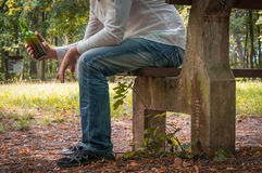 Depressed drunk man with beer bottle sitting on bench Royalty Free Stock Images