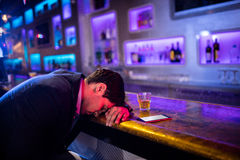 Depressed drunk man sleeping with his head on the table. In bar Stock Image