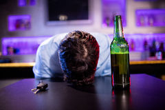 Depressed drunk man sleeping with his head on the table Royalty Free Stock Photos