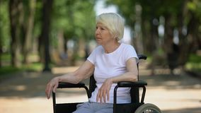 Depressed elderly female sitting in wheelchair at rehabilitation center park stock footage