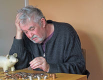 Depressed elderly man counting money. A depressed pensioner with money from his piggy bank. he is counting the money to see if he has enough to pay his bills Stock Image