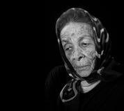 Depressed Elderly Woman on Black Wearing Scarf Stock Photo