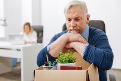 Depressed employee gathering personal documents into the box Stock Image