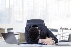 Depressed employee sleeping on the table. Exhausted male entrepreneur sleeping on the table with laptop computer and documents, shot in the workplace Stock Images