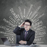 Depressed entrepreneur with work pressure. Young caucasian businessman with work pressure doing his job on laptop computer Stock Image