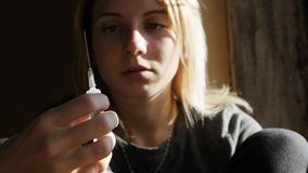 Depressed face of a girl thinking about syringe with heroin. Teen girl. Drug addiction. Depressed face of a girl thinking about syringe with heroin, sitting on Royalty Free Stock Image