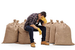 Depressed farmer sitting on a burlap sack Stock Photography