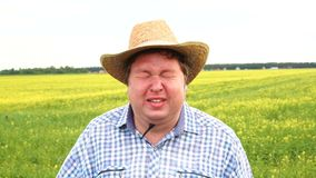 Depressed farmer standing in field and cries, wear cowboy hat on a sunny day. Man in depression, malaise, sadness