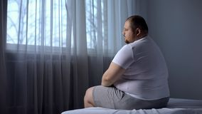 Depressed fat man sitting on bed at home, worried about overweight, insecurities. Stock photo royalty free stock photo