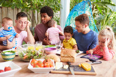 Depressed Father With Baby Talking To Friends stock photo
