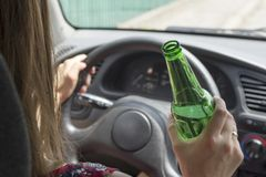 Depressed female driver drinking whiskey from a bottle getting shocked driving a car. Woman drinking alcohol while driving the car stock photography