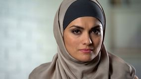 Depressed female in hijab looking sadly in camera, feeling hurt, abused woman royalty free stock images