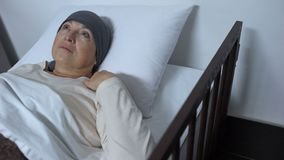 Depressed female patient suffering cancer lying in sickbed, incurable disease. Stock footage stock video