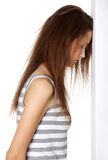 Depressed female teen supporting for the wall. Stock Images