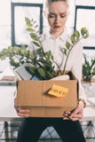 Depressed fired businesswoman holding box with belongings. Young depressed fired businesswoman holding box with belongings Stock Image