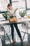 Depressed fired businesswoman holding box with belongings. Young depressed fired businesswoman holding box with belongings Royalty Free Stock Images