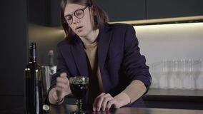 Depressed frustrated Caucasian man pouring red wine into glass and drinking alcohol beverage. Camera approaches to