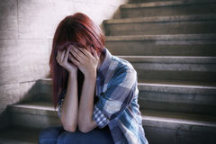 Depressed girl. Girl in adolescent crisis sitting on the steps of a basement, covers her face with her hands. A natural light penetrates from above Stock Image