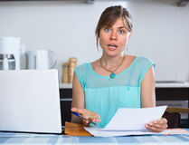 Depressed girl with documents at kitchen Royalty Free Stock Image