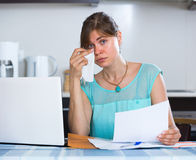 Depressed girl with documents at kitchen Stock Photo