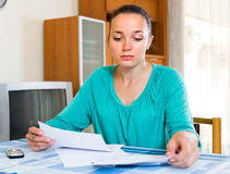 Depressed girl with documents. Sad girl filling out tax forms while sitting at her desk Stock Photos