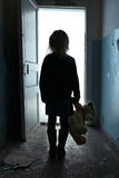 Depressed girl leaving the room. Go away. Poor sad miserable little girl holding her toy and standing turned back while leaving the room Stock Photos