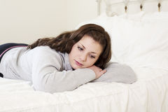 Depressed Girl Lying on Bed Stock Photography