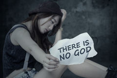 Depressed girl is not trust in GOD. Portrait of lonely teen girl is not trust in GOD, sitting alone and show a paper Stock Photography