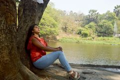 Depressed girl sitting near the lake under a tree. stock photography