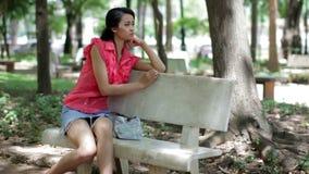 Depressed girl sitting park bench stock video