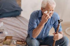 Depressed gloomy man wiping away his tears Royalty Free Stock Image