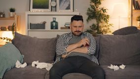 Depressed guy using smartphone holding glass with alcohol sitting at home alone. Depressed bearded guy using smartphone holding glass with alcohol sitting on stock footage