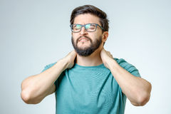 Depressed handsome bearded man touching having a headache. Young depressed handsome bearded man touching his head and having a headache over gray background Stock Images