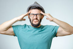 Depressed handsome bearded man touching having a headache. Young depressed handsome bearded man touching his head and having a headache over gray background Stock Photography