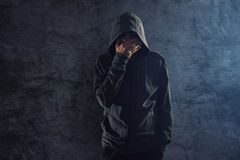 Depressed hooded person leaning on wall and crying Royalty Free Stock Photo