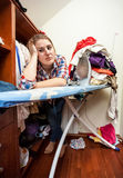 Depressed housewife leaning against ironing board Royalty Free Stock Image