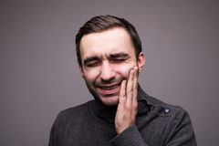 Depressed ill man having toothache and touching cheek isolated on dark background Stock Photography