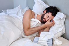 Depressed ill man tissues. Depressed sad sick man with tissues in bed at home Royalty Free Stock Photo