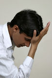 Depressed indian. Depressed and stressed indian sitting with hand on head and thinking Stock Photo
